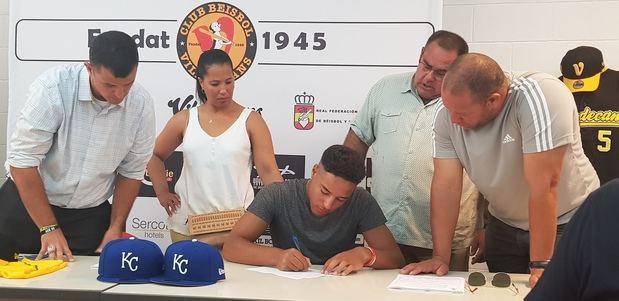 Omar arropado por su familia junto a los representantes del equipo americano en el momento de la firma del contrato.