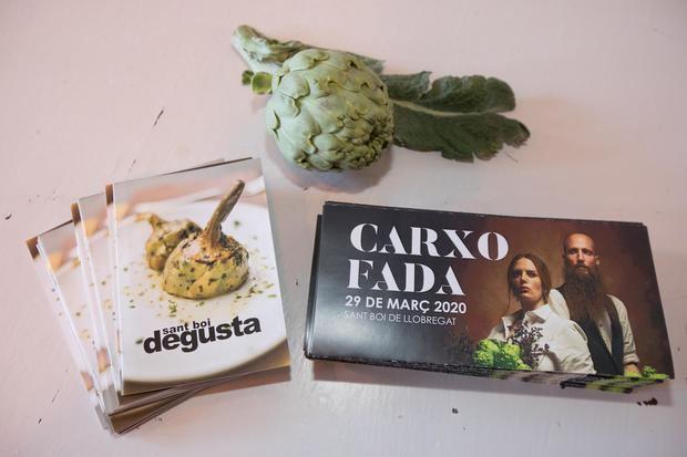 Cartel -derecha- de la 21ª Carxofada de Sant Boi junto al producto estrella y la guía de restaurantes adheridos al mes de la alcachofa en la ciudad