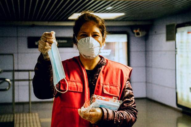Una voluntaria de Creu Roja Cornellà reparte mascarillas en una estación.