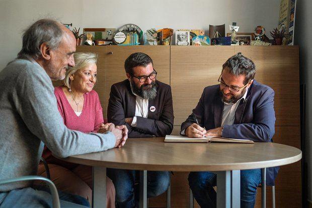 Fernández firmando el Libro de Honor del Ayuntamiento de Collbató, junto al alcalde Solà (a su derecha) y los dos tenientes de alcalde.