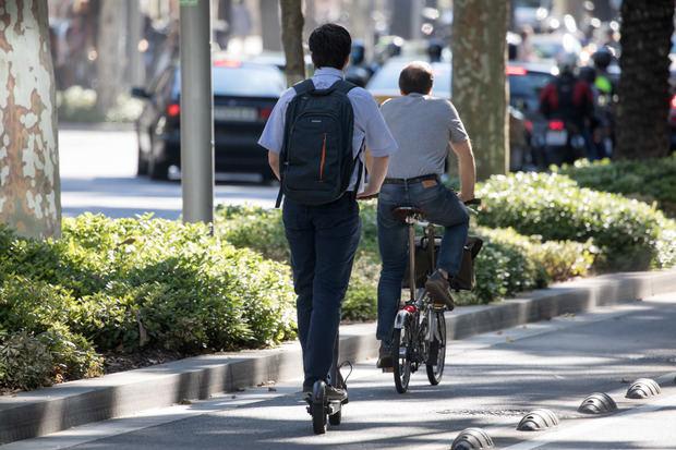 Un patinete eléctrico y una bicicleta circulando por un carril bici.