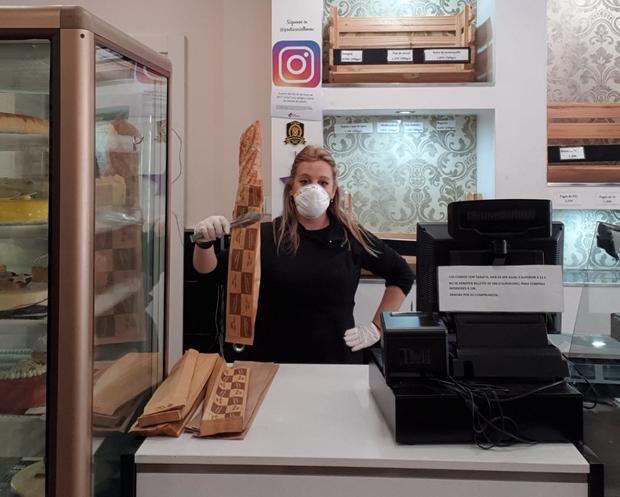 Cristina Espín tras el mostrador de su pastelería, con mascarilla, guantes y pinzas para los alimentos, son algunas de las medidas excepcionales que han adoptado para poder atender a los clientes ante la alerta sanitaria del Covid-19