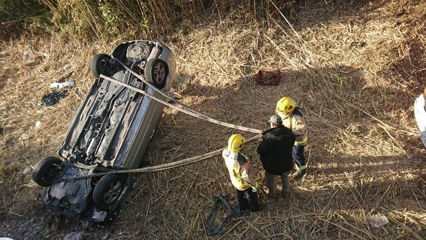 Actuación de los bomberos ante el coche volcado en la riera.