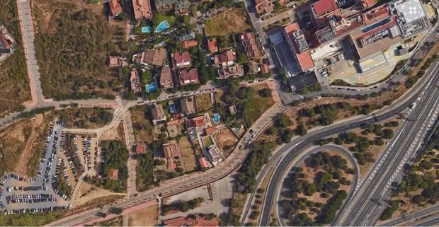 A la part esquerra inferior de la imatge es veu l'aparcament que dóna servei provisioanl pels treballadors, pacients i familiars de Sant Joan de Déu (a dalt a la dreta)