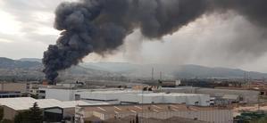 La espectacular humareda del incendio de una fábrica obliga a confinar Sant Feliu