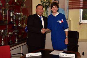 Marc Civit y Henry Sandoval firmando el contrato que lo llevará a jugar en los Toronto Blue Jays.