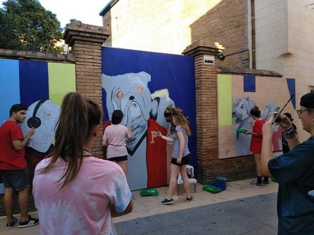 Estudiantes del Institut Mestres de Viladecans dibujando un mural en la fachada de Ca n'Amat