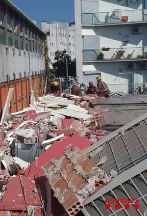 Un equip de Bombers treballa sobre el mur enfonsat