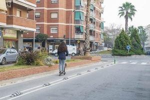 Una mujer transita en patinete eléctrico por El Prat.