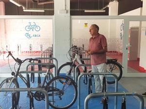 Antonio Poveda, alcalde de Sant Joan Despí y vicepresidente del AMB, en el interior del local comercial explicando los usos de este nuevo aparcamiento para bicicletas que pone en marcha el AMB