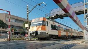 Tren de Rodalies circulando por el paso a nivel de Sant Feliu