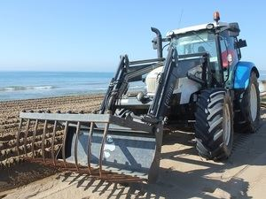 Tractor comenzando las labores de acondicionamiento de las playas metropolitanas en Castelldefels.